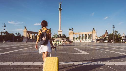 Eine Frau zieht einen gelben Koffer durch die Stadt.