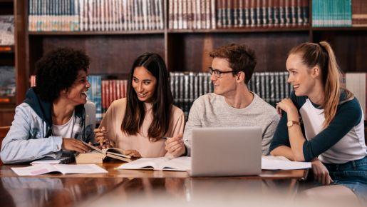 Studierende sitzen an einem Tisch in einer Bibliothek.