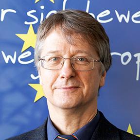 Dr. Klaus Birk vor einem Poster mit der Aufschrift: Wer sich bewegt, bewegt Europa!
