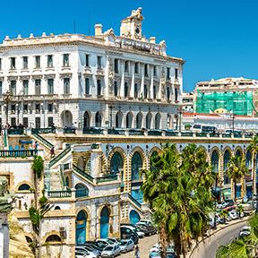 Die Handelskammer, ein weißes Gebäude mit einer Straße davor und Palmen auf beiden Seiten