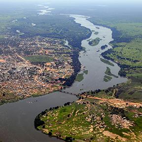 Luftaufnahme von Juba, Stadt an die Linke Seite, einen Fluss in der Mitte und grüne Feld an die rechte Seite