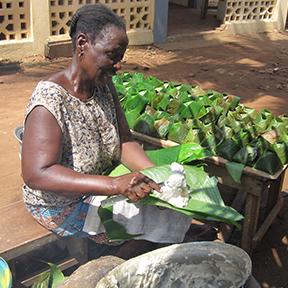 Eine Frau sitzt und bereitet Essen in großen Blättern zu