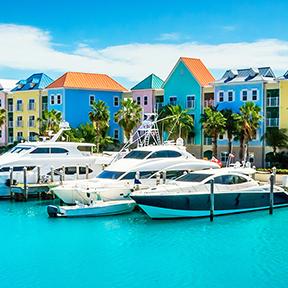 Bild einer bunten Häuserfassade auf den Bahamas vor der Boote stehen