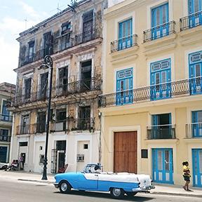 Ein gelbes und ein weißes Haus an einer Straßenecke. Vor ihnen steht ein blaues Auto.