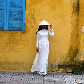 Eine Frau mit weißen Kleid und einem asiatischen Kegelhut steht vor einem gelben Haus mit blauen Fensterläden.