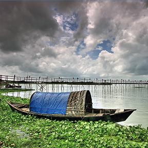 Ein Boot liegt im Wasser und im Hintergrund ist eine kleine Holzbrücke zu sehen