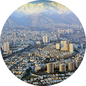 Die schneebedeckte Alborz-Gebirgskette und das Sonnenlicht schmücken die Landschaft des smoggy Teheran