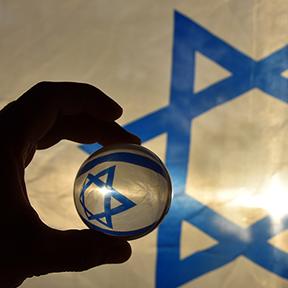 Im Hintergrund hängt die israelische Fahne. Eine männliche Hand hält eine Glaskugel, in der sich der Stern der Flagge spiegelt.