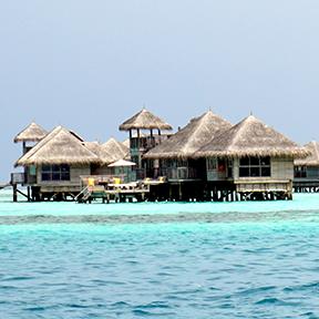 Eine Gruppe von Überwasser-Bungalows im Meer vor den Malediven.