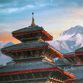 Zwei Türme eines Tempels. Im Hintergrund schneebedeckte Berggipfel