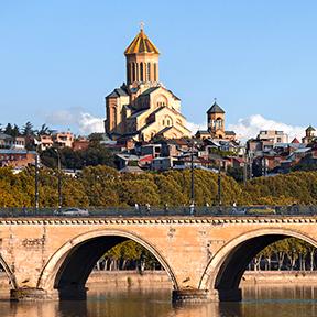 Im Hintergrund sieht man die Sameba-Kathedrale von Tiflis. Umringt von einer Stadt. Im Vordergrund ist eine Brücke zu sehen.