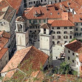 Die Stadtmitte von Montenegro wird von zwei Türmen und vielen weißen Häusern mit roten Ziegeldächern gebildet.