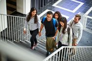 Studierende gehen eine Treppe im Universitätsgebäude hoch