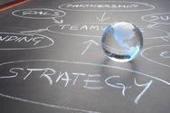 Glas-Weltkugel auf Tafel mit Stichwörtern Strategie und Teamwork
