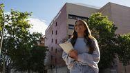 Eine Frau geht durch das Universitätsgelände.