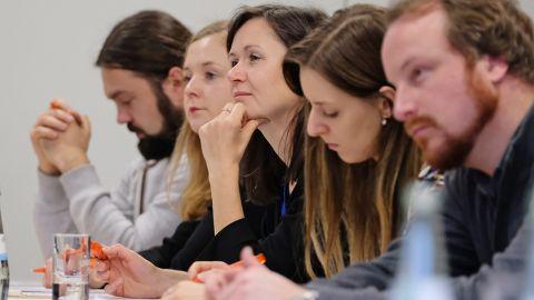 Eine Gruppe Menschen sitzt an einem Tisch und macht Notizen - BIDS