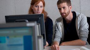 Ein Mann und eine Frau sitzen und gucken einem Computerbildschirm an. - Ausbildung