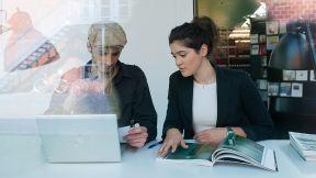 Ein Mann und eine Frau sitzen zusammen und gucken einen Laptop an.