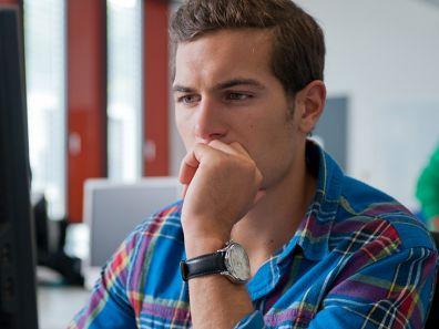 Ein Mann in karierten Hemd schaut nachdenklich auf den Bildschirm seines PC's. - Newsletter