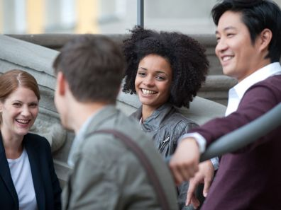 Vier lachende Studenten auf einer Treppe - Stipendien