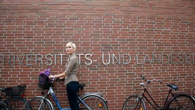 Eine Frau mit Fahrrad steht vor einem Universitätsgebäude - Die Förderung nach deutschen Bundesländern